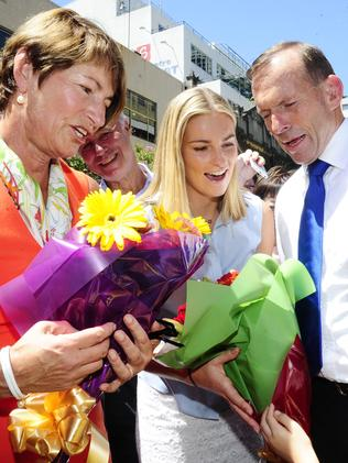 Margie, Bridget and Tony Abbott receive flowers in Chinatown in Sydney on the eve of a leadership spill. Picture: Damian Shaw