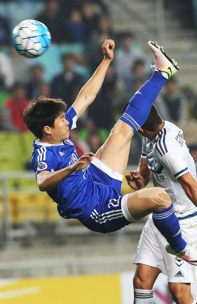 Daniel Georgievski (R) fights for the ball with Kwon Chang-Hoon (L).