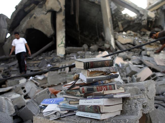 Hit ... Palestinian men collect copies of Islam's holy book the Koran from a destroyed mosque following an Israeli military strike in the Nusseirat refugee camp in the central Gaza Strip. Pic: THOMAS COEX