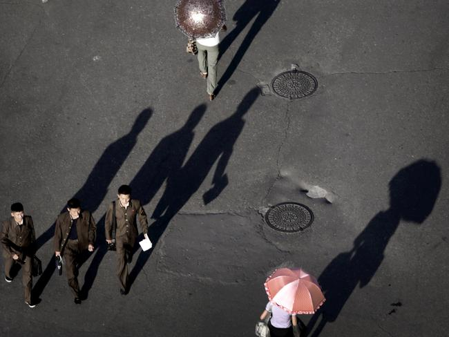 Long shadows are cast by the evening sun as North Koreans make their way home after a day's work.