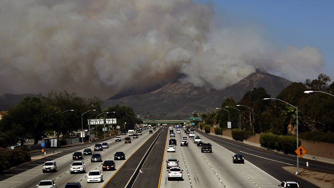 Smoke billows over along highway US 101 near Thousand Oaks, California. Authorities ordered evacuations of a neighbourhood and a university about 80km west of Los Angeles where a wildfire is raging close to subdivisions. Picture: AP