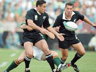 NZ All Blacks centre Frank Bunce lets ball out as tackled by South Africa's Springboks player during Rugby World Cup final Ellis Park Johannesburg 24 Jun 1995 Walter Little (R). Sport / Rugby Union / Action RWC o/seas