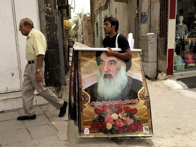 Call for volunteers ... a Baghdad vendor sells posters of Shiite spiritual leader Grand Ayatollah Ali al-Sistani, who has called for Iraqis to defend the city. Picture: Khalid Mohammed