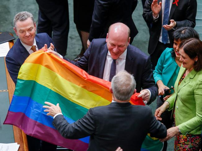 Malcolm Turnbull is handed a rainbow flag on the floor of the House of Representatives. Picture: AFP/Sean Davey
