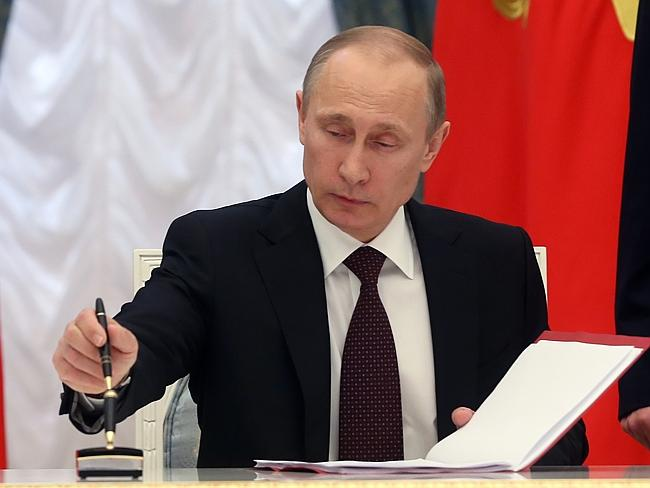 Russian President Vladimir Putin signs bills making Crimea part of Russia in the Kremlin