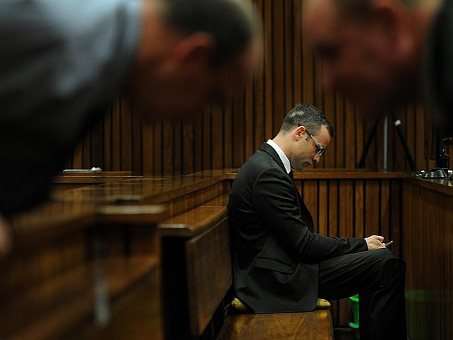 Defence witnesses ... Oscar Pistorius sits in the dock inside court in Pretoria as members of his defence team confer over the benches. Picture: AP