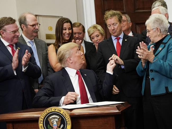 US President Donald Trump hands a pen to Republican Senator Rand Paul who has spoken against his plans to repeal and replace ObamaCare. Picture: AFP