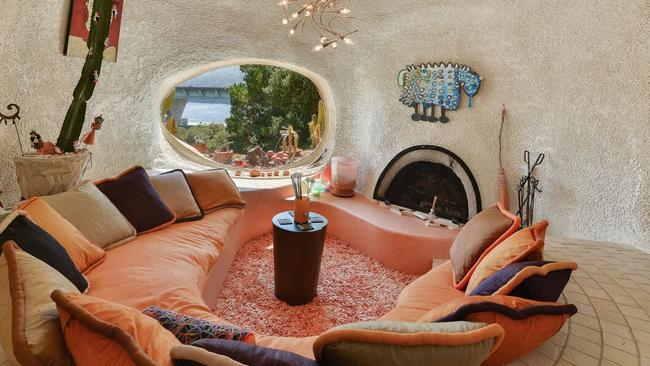 """The sunken """"conversation pit room"""" has circular seating, a domed ceiling, a fireplace, and an amoeba-shaped window cut specifically to hide the freeway while showcasing the Crystal Springs Reservoir. Picture: Judy Meuschke Alain Pinel Realtors."""