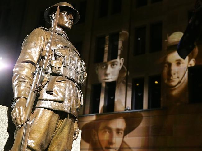 Projections seen on surrounding buildings at the Sydney Anzac Day dawn service added to the atmosphere in Martin Place. Picture: Bill Hearne