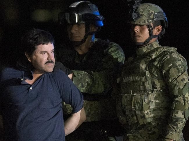 "Mexican drug lord Joaquin ""El Chapo"" Guzman is escorted by army soldiers to a waiting helicopter, at a federal hangar in Mexico City. Picture: AP"