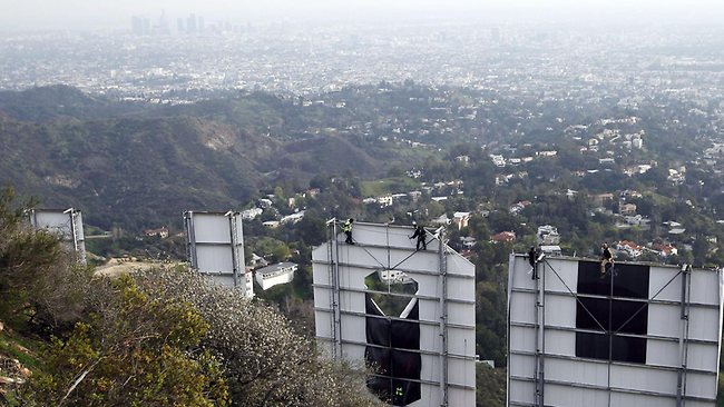 It looks better from the other side. Workers tidy up the Hollywood sign with a smoggy view of LA below. (AP Photo/Damian Dovarganes)