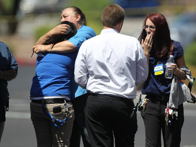 Walmart employees hug outside a store after two assailants shot dead three people. Picture: AP Photo/Las Vegas Review-Journal