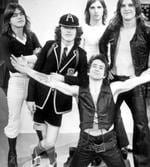 <p>Lead singer Bon Scott kneeling flanked by fellow members of band AC/DC including Phil Rudd, Malcolm Young and Angus Young in undated photo.</p>