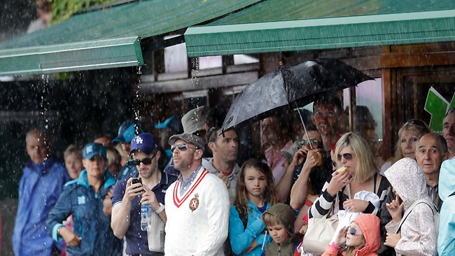 Tennis fans shelter under an awning on Centre Court during a rain delay at the All England Lawn Tennis Club in Wimbledon.