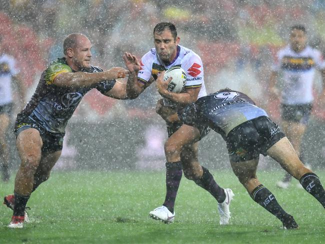 Cameron Smith (centre) is tackled by Matthew Scott (left) and Jake Granville (right).