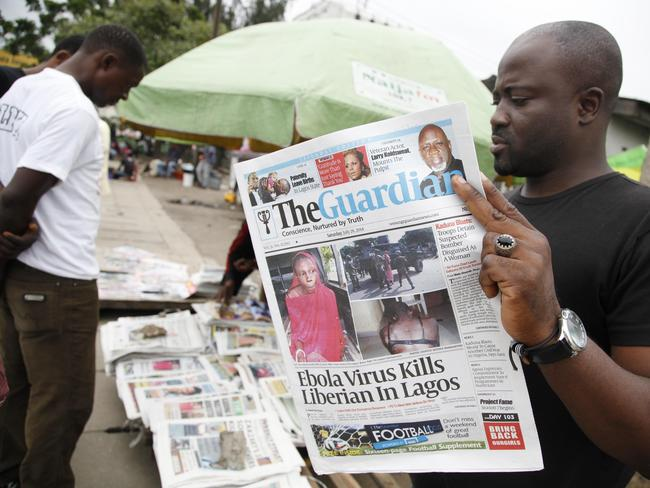 Spreading alarm ... A man reads a local newspaperson a street with the headline Ebola virus kills Liberian in Lagos, in Lagos Nigeria, at the weekend.