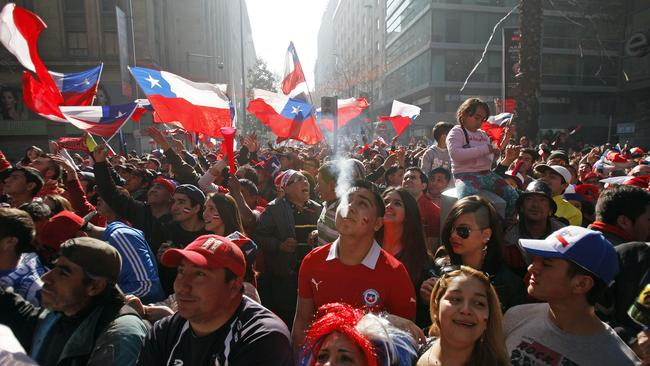 Chile soccer fans watch their team's World Cup round of 16 match with Brazil on TV in Santiago.