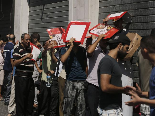 Rationing ... Palestinian men wait in line to buy bread outside a bakery in Gaza City. Picture: AFP