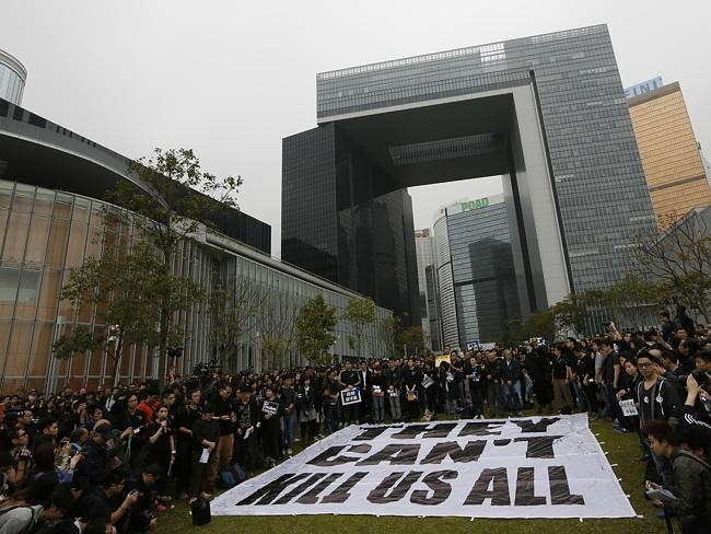 """Defiant ... journalists and their supporters stand around a huge banner reads """" They can'"""
