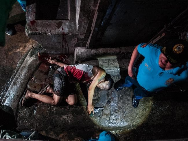 Police guard the body of an alleged drug dealer killed in a shootout with swat teams during a drug raid on July 21 in Manila. Picture: Getty Images