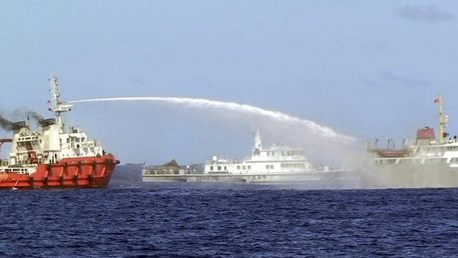 A Chinese ship, left, shoots water cannon at a Vietnamese vessel (right) while a Chinese Coast Guard ship (centre) sails alongside. Chinese ships are ramming at Vietnamese vessels trying to stop Beijing from setting up an oil rig in the South China Sea. Picture: AP/Vietnam Coast Guard