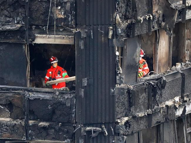 Emergency services work on the middle floors of the charred remnains of the Grenfell Tower block. Picture: AFP
