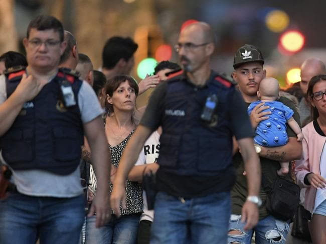 Spanish police officers accompany people out of the area following the attack. Picture: Lluis Gene