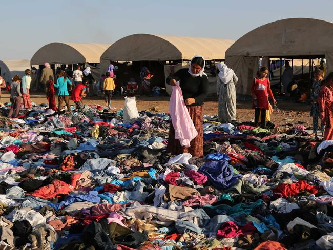 Displaced Iraqis from the Yazidi community look for clothes to wear among items provided by a charity organisation at the Nowruz camp, in Derike, Syria, Pic: AP.