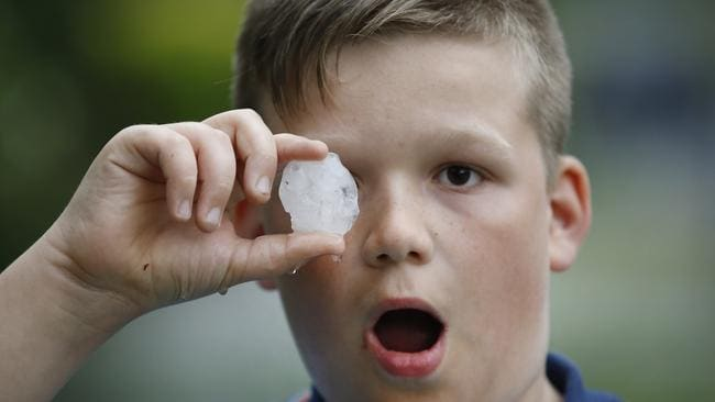 Cooper 10, holds one of the large hail stones that pelted down. Picture: David Caird