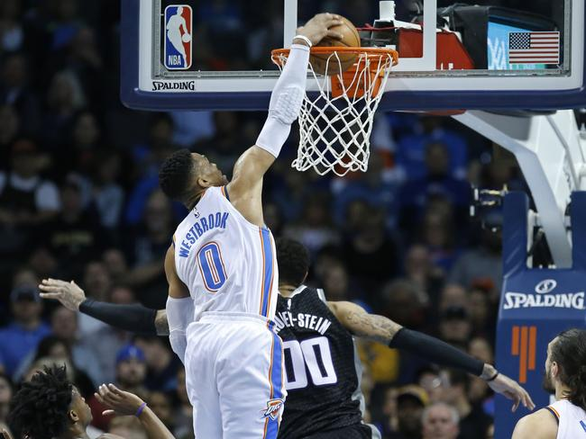 Russell Westbrook dunks over Sacramento Kings centre Willie Cauley-Stein. (AP Photo/Sue Ogrocki)