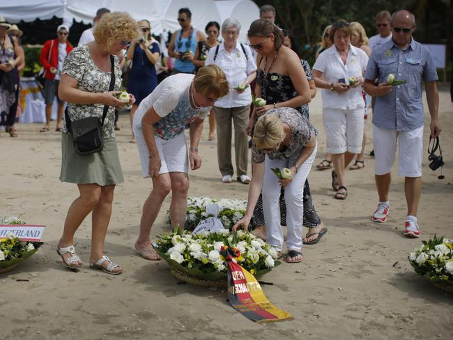 Relatives of victims of the Asian tsunami lay white roses on the beach during a commemoration and religious ceremony for German, Austrian and Swiss victims in Khao Lak, Thailand. Picture: AP / Wong Maye-E