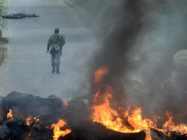 Attacks continue ... an armed pro-Russian man walks past burning debris at a checkpoint in the southern Ukrainian city of Slavyansk. Picture: VASILY MAXIMOV