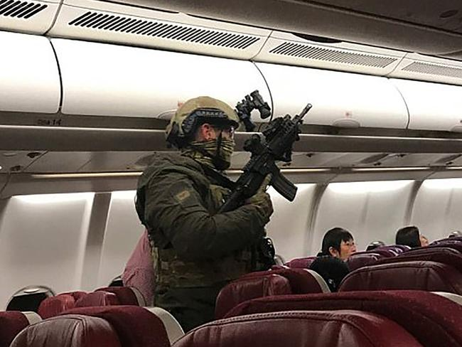 Heavily-armed police board flight MH128 to arrest a restrained passenger who claimed to have a bomb. Picture: AFP/Andrew Leoncelli