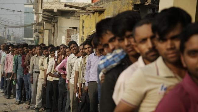 Locals queue to exchange discontinued currency outside a bank in New Delhi.