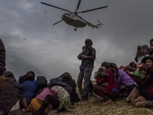 QWEEKEND - WORLD PRESS PHOTO AWARDS - 3—Gumda, Nepal. Saturday, May 09, 2015: Nepalese villagers look on as they watch a helicopter picking up a medical team, dropping aid at the edge of a makeshift landing zone on May 9, 2015 in the village of Gumda, Nepal. On the 25th of April, just before noon local time, as farmers were out in fields and people at home or work, a devastating earthquake struck Nepal, killing over 8,000 people and injuring more than 21,000 according to the United Nations Office for the Coordination of Humanitarian Affairs. Homes, buildings and temples in Kathmandu were destroyed in the 7.8 magnitude quake, which left over 2.8 million people homeless, but it was the mountainous districts away from the capital that were the hardest hit. Villagers pulled the bodies of their loved ones from the rubble by hand and the wails of grieving families echoed through the mountains, as mothers were left to bury their own children. Over the following weeks and months, villagers picked through ruins desperate to recover whatever personal possessions they could find and salvage any building materials that could be reused. Despite relief teams arriving from all over the world in the days after the quake hit, thousands of residents living in remote hillside villages were left to fend for themselves, as rescuers struggled to reach all those affected. Multiple aftershocks, widespread damage and fear kept tourists away from the country known for its searing Himalayan peaks, damaging a vital climbing and trekking industry and compounding the recovery effort in the face of a disaster from which the people of Nepal continue to battle to recover.