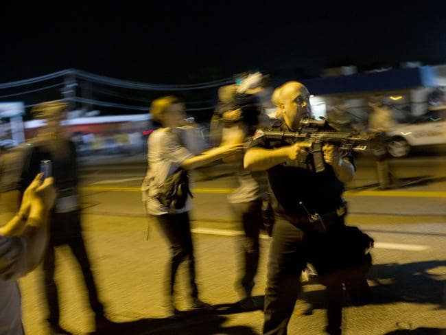 Suspended ... Lieutenant Ray Albers points an assault rifle at a protester in Ferguson, Missouri. Picture: Aaron P Bernstein