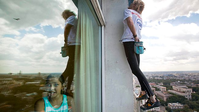 Alain Robert reaches into his chalk bag as he scales the hotel. Picture: AP