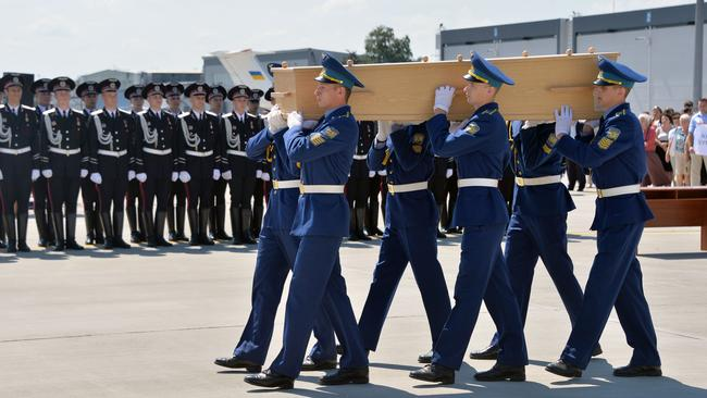 On the move ... Ukrainian soldiers carry a coffin with the remains of a victim of the Malaysia Airlines flight MH17 crash to a military plane during a ceremony at the airport of Kharkiv, Ukraine. Picture: Genya Savilov