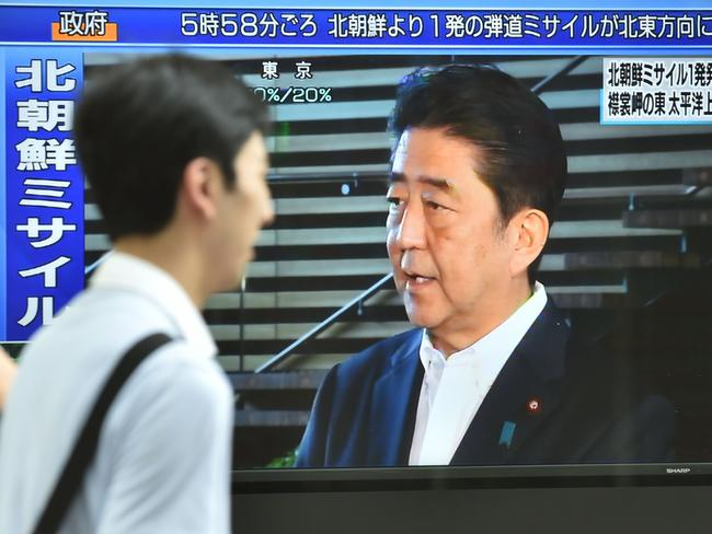 Pedestrians walk in front of a television screen displaying Japan's Prime Minister Shinzo Abe speaking to the media after the North Korean missile test. Picture: AFP photo