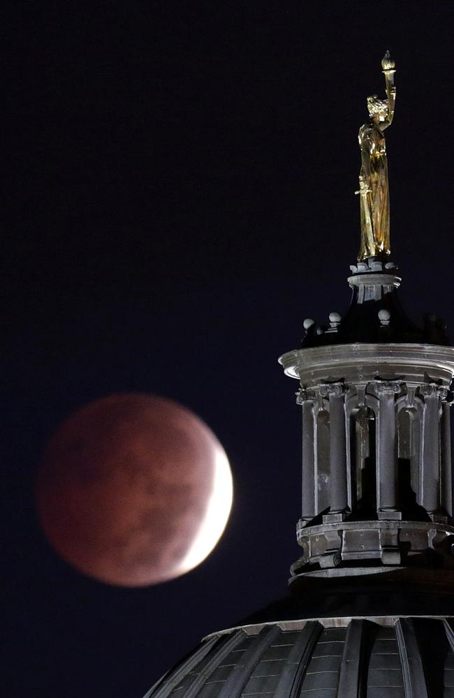 "A lunar eclipse is seen near a statue entitled ""Enlightenment Giving Power"" by John Gelert, which sits at the top of the dome of the Bergen County Courthouse in Hackensack, New Jersey. Picture: AP"