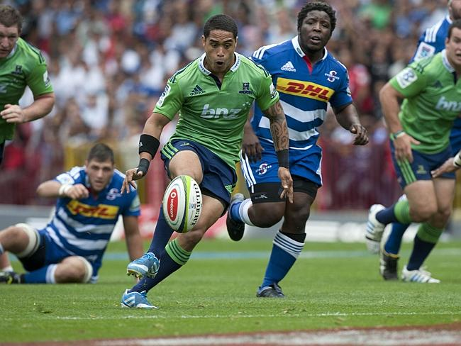Highlanders fly half Aaron Smith (Center L) kicks the ball just before scoring a try against the Stormers.