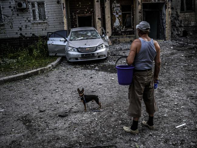 Devastation in Donetsk ... a man and his dog inspect an area that had been shelled on July 29. Picture: Bulent Kilic