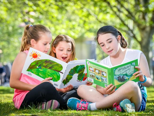 Casey Boyd, 9, Madison Boyd, 4 and Tia Dempsey, 9 read The Very Hungry Caterpillar and Hair Maclary. Picture: Jake Nowakowski