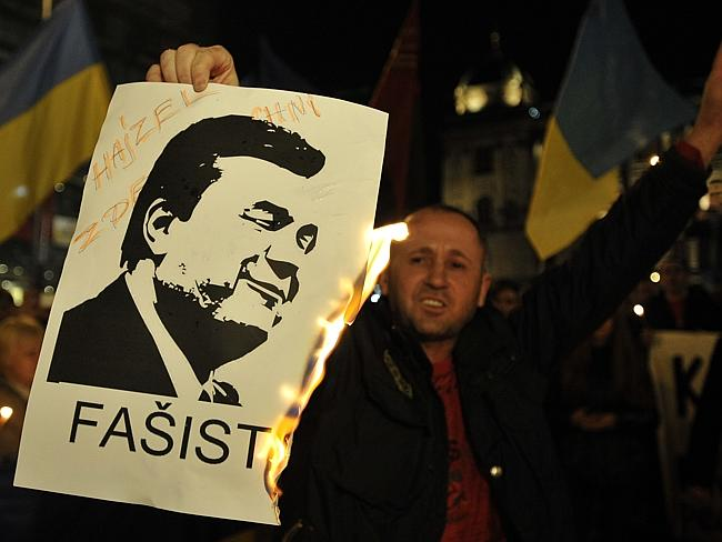 Heated issue ... a protester sets light to a portrait of former Ukrainian President Viktor Yanukovich during a protest in Prague´s Wenceslas Square. Picture: Michal Krumphanzl