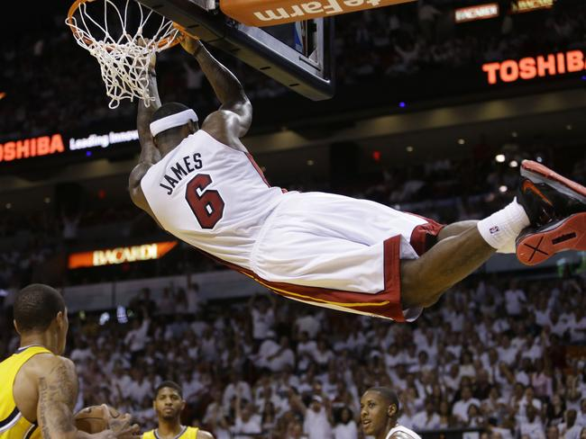Miami Heat forward LeBron James (6) hangs from the basket after dunking the ball.