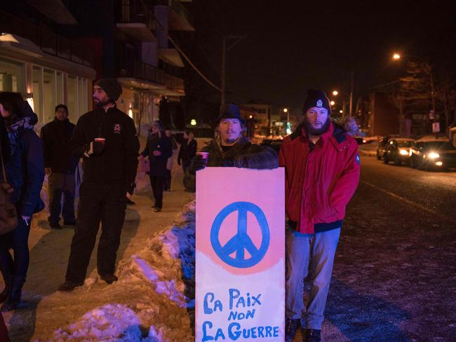 People stand with a peace sign near the mosque where two gunmen opened fire. Picture: AFP/Alice Chiche