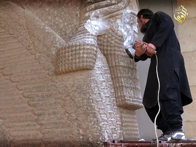 An IS militant destroying the statue of Lamassu, an Assyrian deity, with a jackhammer in the northern Iraqi Governorate of Nineveh. AFP PHOTO / HO / Media Office of the Nineveh branch