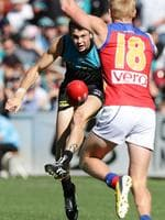 Round 4: Jasper Pittard kicks despite pressure from Lion Nick Roberrson. Picture: Sarah Reed.