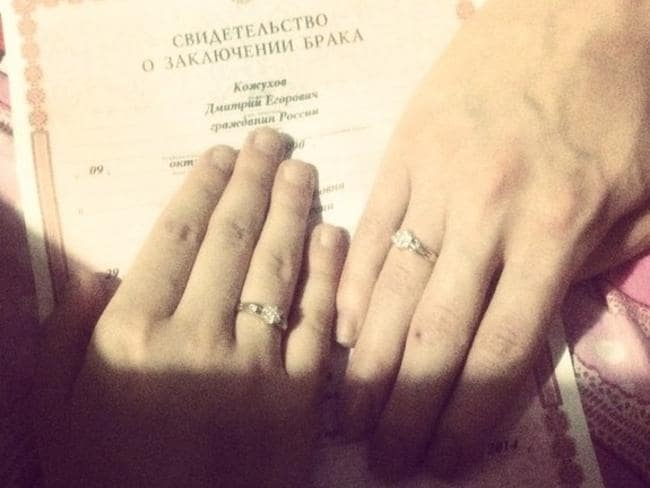 Officially husband and wife: the couple show off their wedding certificate and matching rings.