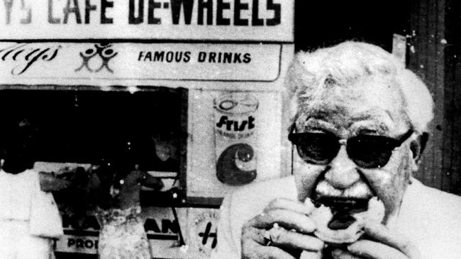 Kentucky Fried Chicken founder Colonel Sanders enjoys a pie from Harry's Cafe De-Wheels in 1974.